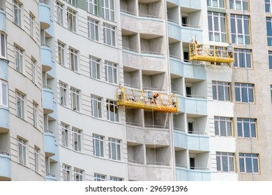 Kiev/Ukraine - July 13, 2015 - Construction of modern residential building  in the Obolon district of Kiev the capital of Ukraine. Workers are painting the facade