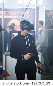 KIEV,UKRAINE-28 OCTOBER,2018: Man uses modern HTC Vive VR headset for playing virtual reality game at VR Expo event indoor.