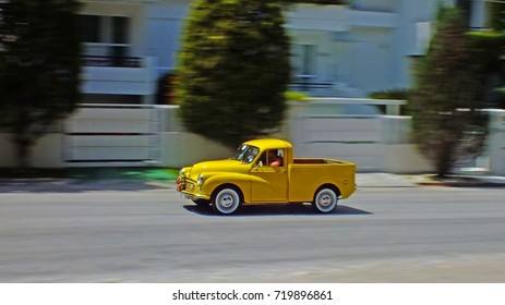 KIFISSIA, ATHENS, GREECE, MAY 1, 2017. Panning shot of a yellow Morris Minor 1000 Pickup during a classic car event organized by the Classic Car Club of Greece-FILPA.