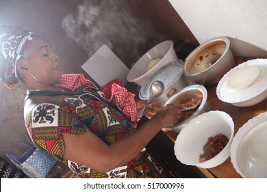 KIGALI, RWANDA - CIRCA AUGUST 2015: The talented chef Aminatha finishes preparing the traditional Rwandan dishes she was cooking to serve them to her guests.