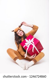 Kigurumi pajamas. Cute young woman in pajamas sitting with big red present box and having fun on white background .