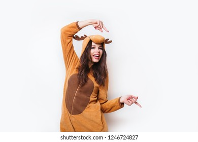 Kigurumi pajamas. Funny young woman in pajamas standing and showing to the side on white background .