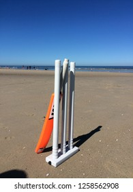 Kijkduin beach, the Netherlands - May 25 2017: cricket stumps, wickets and bat after a day of beach cricket on the dutch coast; more people on the beach due to good weather