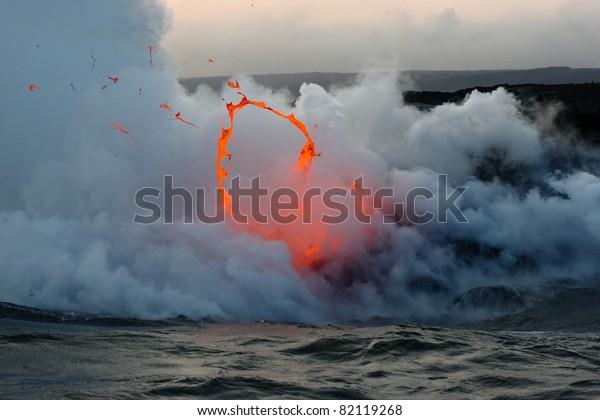 Kilauea volcano lava flow spitting into the air and ocean. Hawaii Volcanoes National Park.