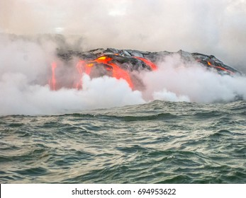 Kilauea Volcano, also Kilauea Smile because from 2016 seems to smile, erupting lava into Pacific Ocean, Big Island, Hawaii. View from the boat of lava rivers into the sea. Kilauea erupting since 1983.