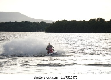 KILLADEAS, ENNISKILLEN, IRELAND - JULY 2018: Man riding a jetski on Lough Erne