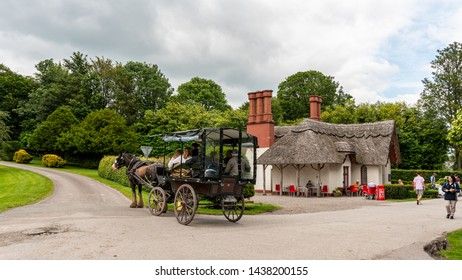 Killarney, Co. Kerry, Ireland - June 26, 2019: Tourists in a horse drawn traditional jaunting car passing a coffee shop on a tour through the grounds of the National Park.