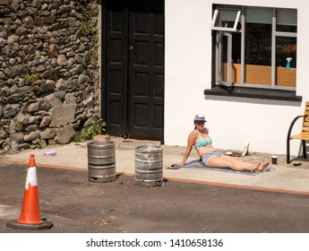 Killarney, County Kerry, Ireland. 29 June 2018. Young woman enjoying sunbathing in funny way on concrete surface in a backyard. Urban sunbathing.