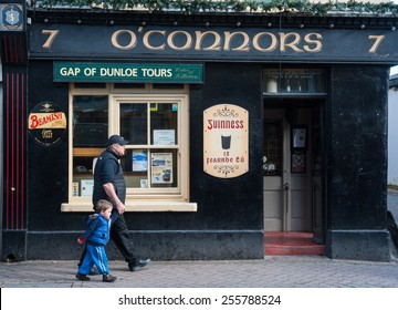 KILLARNEY, IRELAND - 14TH FEBRUARY 2015: A man and child walk past O'conners traditional Irish pub in the town of Killarney, Killarney is well known for its traditional Irish pubs.