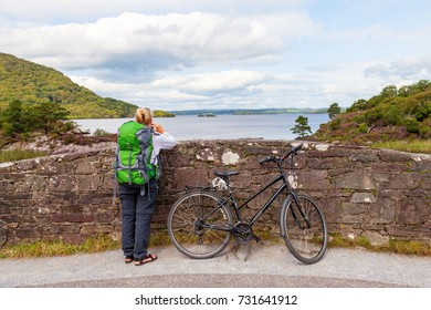 KILLARNEY NATIONAL PARK, KERRY, IRELAND - AUGUST 22, 2017: Mature female tourist with bicycle stops at Brickeen Bridge to admire the view over Lough Lein