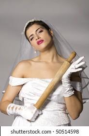 Killer bride photo series. Bridezilla with wooden rolling pin. Studio shot