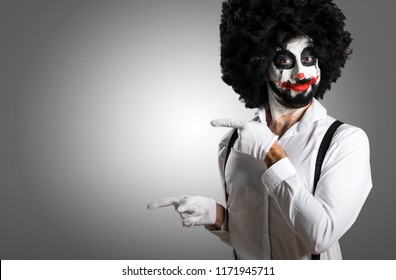 Killer clown pointing to the lateral on textured background