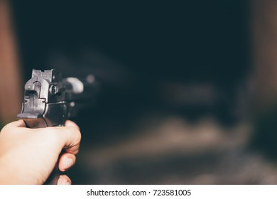Killer with gun, a gun ready to shoot, aiming at the target, Focus on weapon