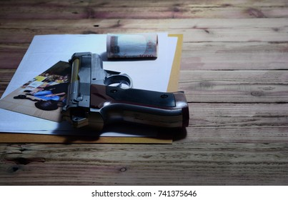 the killer job,a handgun with photo ,money and paper on the wooden table