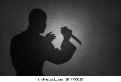killer or terrorist with knife, shadow on wall, offence act assassination concept