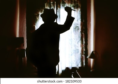 Killer's silhouette with knife in a dark room