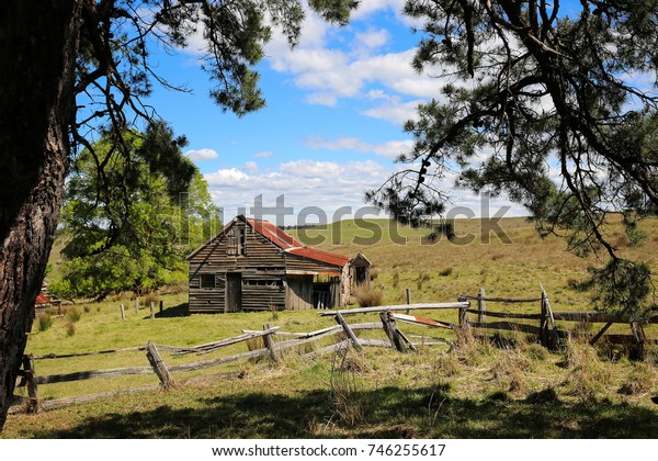 KILMORE, NEAR MELBOURNE, AUSTRALIA : 23 OCTOBER 2017 - An old, weathered barn with its tumbledown fence stands in a field framed by a large pine tree.