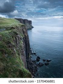 Kilt rock and Mealt falls on Isle of Skye, Scotland, UK.Moody sky over dramatic Scottish coastline with high rocky cliffs and turquoise sea.Popular tourists attraction.Coastal landscape scene.