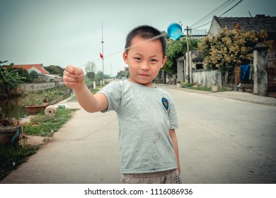 Kim Son, Ninh Binh/ Vietnam - 03 31 2018: a boy playing with his yoyo at Kim Son village, Ninh Binh, Vietnam
