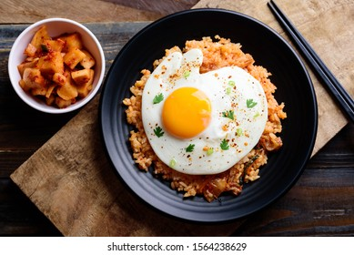 Kimchi fried rice with fried egg on top and fresh kimchi on wooden background, Korean food, top view