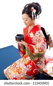 ?apanese kimono woman drinking japanese tea on white background