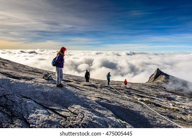 KINABALU, MALAYSIA FEB 8, 2014 : Trekkers walking on the top of Mt.Kinablu with view of South peak