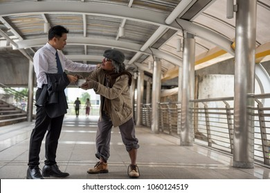 Kind Business man giving one dollar bill money to old beggar or homeless guy at city walk in urban town. Poverty and social issue concept. Give and share with sympathy