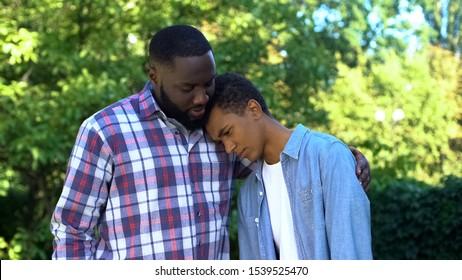 Ein netter Vater umarmt jugendlichen Sohn, der Schuldzuweisungen, Erziehung von Kindern, Elternschaft einräumt
