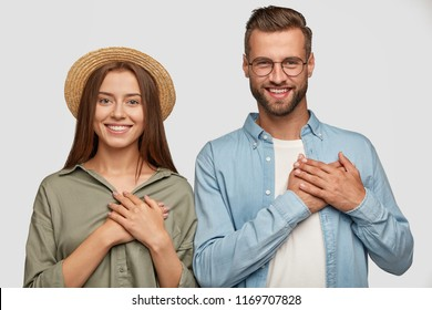Kind hearted friendly looking young woman and man keep both palms on chest, dressed casually, express gratitude and good feeling, stand next to each other, isolated over white studio background.