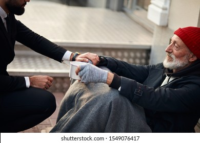 Kind man help beggar male sitting on street begging, cold weather. Pity male need money, food, shelter. Beggar with grey gloves