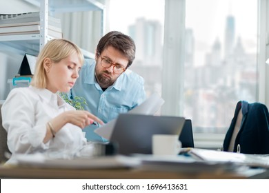 Kind manager giving feedback to young female intern in a busy downtown office. New employee asking for guidance on current project.