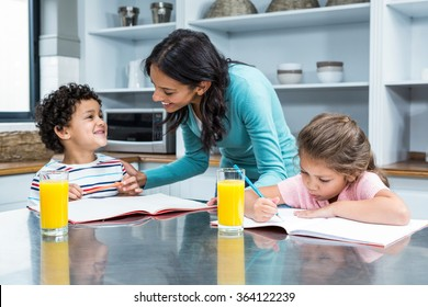 Kind mother helping her children doing homework in kitchen
