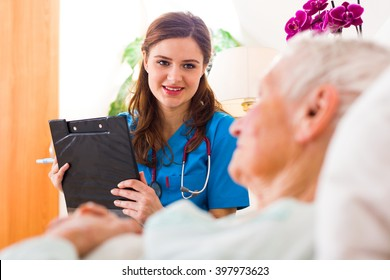 Kind nurse with clipboard in her hands registering senior woman's healthcare stats.