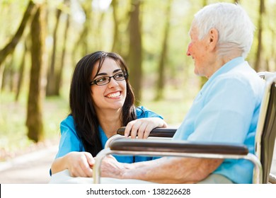 Kind nurse laughing with elderly patient in wheelchair.