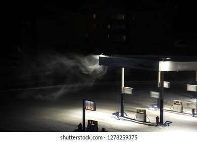 Kind on a deserted gasoline station in the winter at night, snowstorm