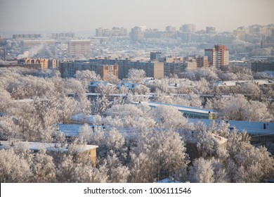 Kind on a winter city. The roofs of the houses, the trees in the snow, the city's skyline. Concrete jungle.