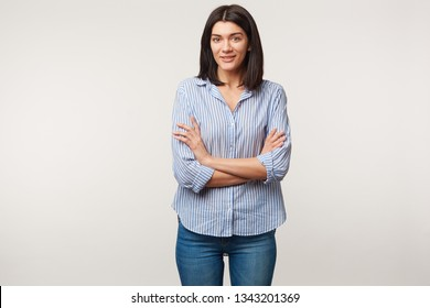Kind pleasant young dark-haired female standing with arms crossed dressed in jeans and striped shirt mouth opened as talking with someone, feeling a little ill at ease, isolated over white wall