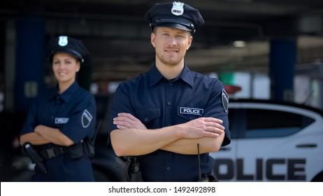 Freundliche Polizisten lächeln in der Nähe der Polizeiwache, bereit zu helfen, Ordnung