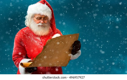 Kind Santa Claus reading vintage paper with wishes on blue background. Merry Christmas & New Year's Eve concept. Copy space.
