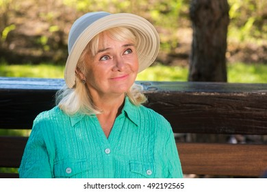 Kind senior woman. Lady in hat smiling. Live this life in joy. Warm and sunny days.