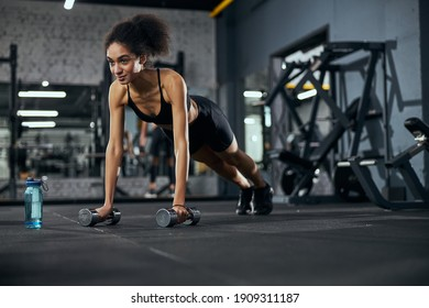 Kind sportswoman leaning on dumbbells while looking forward during workout