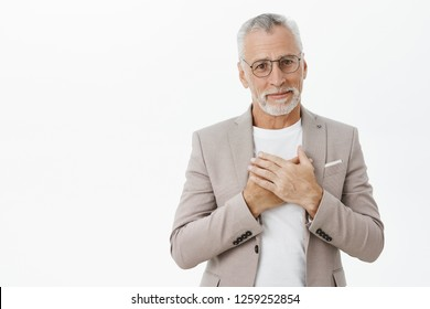 Kind and tender touched cute senior grandfather with white hair and beard in suit and glasses pressing palms to heart smiling sincere being grateful and thankful for gift and nice words