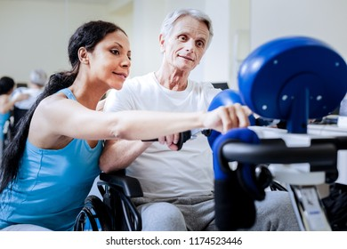Kind trainer. Smart calm attentive trainer of a rehabilitation center helping her disabled aged patient in a wheelchair to understand the procedure of their trainings