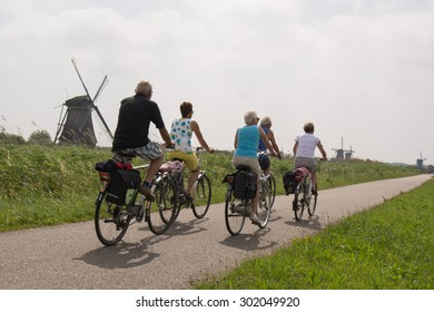 KINDERDIJK, NETHERLANDS - 17 JULY 2015: enjoying later life: group of friends cycling past windmills on a summer day