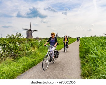 KINDERDIJK, NETHERLANDS - AUG 29: Cycling road in Kinderdijk, Netherlands on August 29, 2013. The windmills of Kinderdijk are one of the best-known Dutch tourist sites.