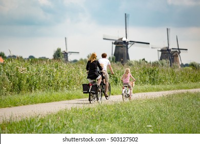 Kinderdijk The Netherlands - June 14: Happy family with two children ride bicycles in an alley near Windmills of Kinderdijk UNESCO World Heritage. in Kinderdijk  Netherlands on June 14, 2015.