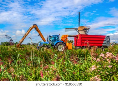 KINDERDIJK, NETHERLANDS - SEPTEMBER 04, 2015: tractor with mower in action at the famous windmills. They are one of the best-known Dutch tourist sites and UNESCO world heritage site