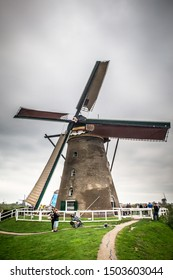 KINDERDIJK, NETHERLANDS - SEPTEMBER 3, 2019:  View of historic Dutch Windmill with people visiting visible