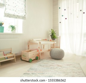 Kindergarten apartment with easel chair and table for painting. children room interior. Kids room with wooden desk and shelf with books. White sunny room with big window for young child. Home interior