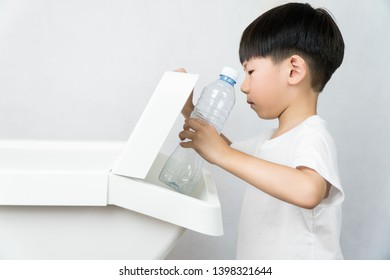 A kindergarten boy learning to sorted plastic water bottles into the recycle bin separated from others. Waste segregation, Single-use plastic problems, Environmental awareness, Zero waste concept.
